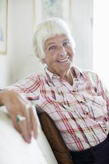 Portrait of smiling senior woman sitting on sofa