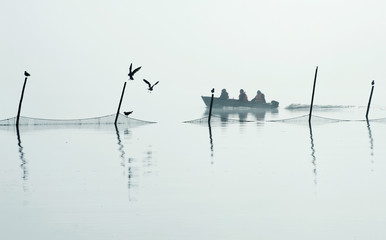 People on boat near fishing net