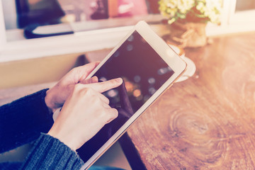 asian woman hand holding tablet and using tablet in coffee shop
