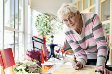 Elderly woman painting