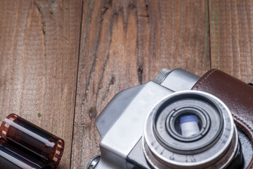 Old retro camera on vintage wooden boards abstract background. Copy space for text