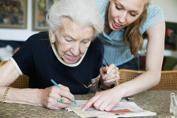 Two women solving crosswords together