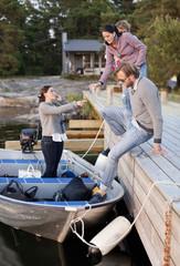 Friends loading luggage in motorboat