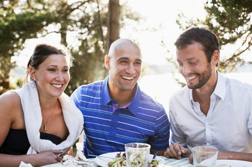 Three friends smiling together while dinning outdoors