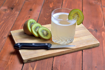 Cocktail and kiwi on a wooden background, summer composition.