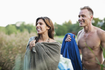 Cheerful heterosexual couple with towel on beach together