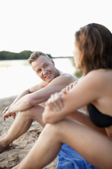 Handsome mid adult man with woman sitting on beach towel