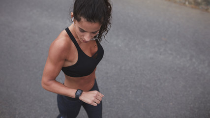 Female athlete checking her smart watch after a run
