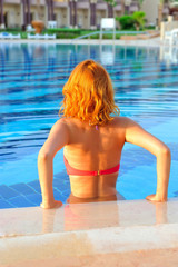 Young redheaded woman relaxing in the pool. View from the back