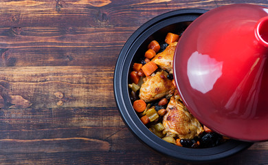 Tagine with cooked chicken and vegetables. Traditional moroccan cuisine. Wooden background