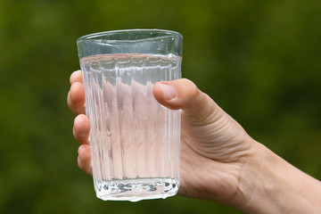 hand holding glass with water