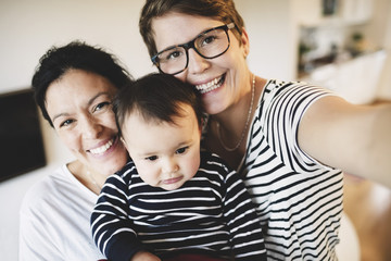 Portrait of smiling lesbian couple with toddler at home