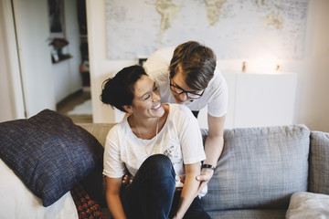 Smiling lesbian couple enjoying in living room at home