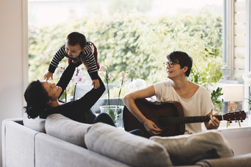 Mother enjoying with baby girl while woman playing guitar at home