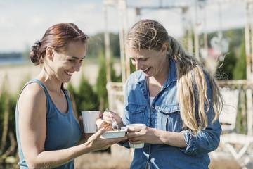 Cheerful female friends enjoying food with coffee in back yard