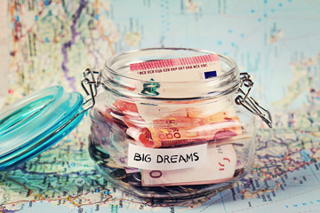 Piggy bank woth words Big Dreams on travel map. Saving money for travel. Dreaming Concept