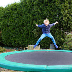 Happy kid plays outdoors in garden jumping high in the sky on trampoline. Active teenager boy having fun outdoors at early spring day. Healthy lifestyle concept.