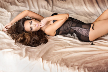 Sexy brunette girl posing in bed