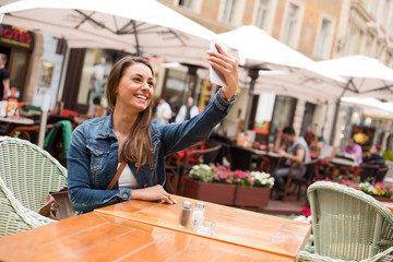 Young woman taking a selfie sitting outside a restaurant