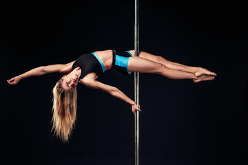 Pole dancer. Young pretty woman on black background