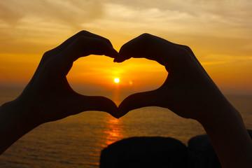 Love shape hand silhouette, sun set on the beach background.