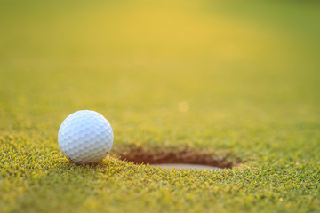 Golf ball on lip of cup  in course