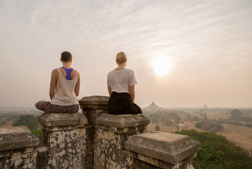 Two beautiful women Yoga and Meditation on Old Bagan Pagoda sunr