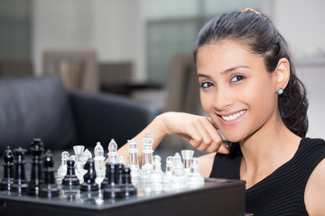 Closeup portrait, thinking woman in black shirt playing chess, wondering next move, isolated indoors background
