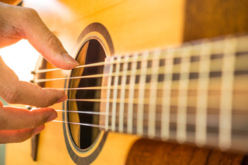Man's hands playing acoustic guitar.