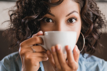 Eastern brunette curly girl drinking and smelling a cup of tea o