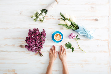 Woman hands on table with cup of coffee and flowers