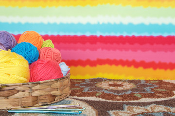 Balls of colorful yarn in a wicker basket on colorful carpet with rainbow stripped background wallpaper.