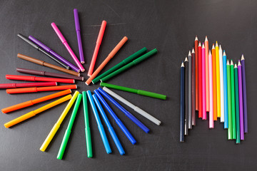 """A lot of colorful felt-tip pens in circle and colorful  pencils in row on the black school chalkboard as background, concept """"Back to school"""""""