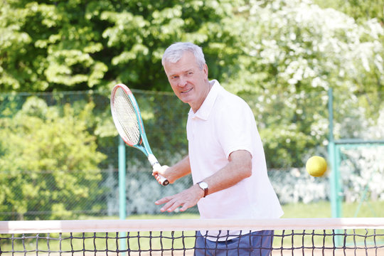 Win the game. Senior trainer man playing tennis