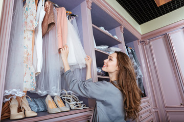 Young woman searching what to wear in a wardrobe