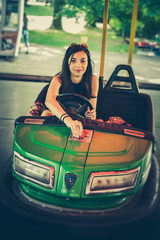 Cute young woman having fun in electric bumper car in amusement park
