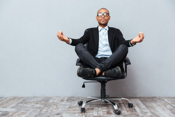 Relaxed african young man sitting and meditating on office chair Fototapete