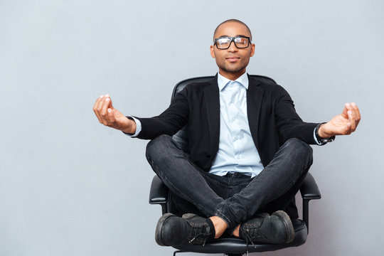 Attractive young man in glasses meditating on office chair