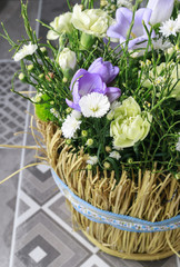 Basket with carnation and freesia flowers.
