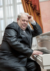 Mature musician playing a white piano