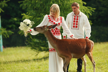 Pretty couple dressed in red and white colors stroke a deer in p