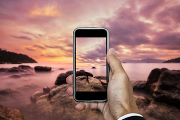 Hand holding smart phone taking photo of sunset landscape in vertical composition, in summer vacation time