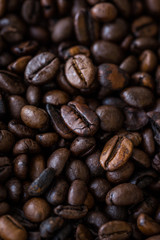 Vertical view of roasted coffee beans. Macro shot of coffee beans with selective focus. Shallow depth of field.