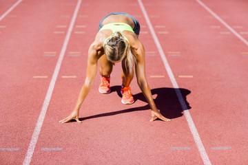 Female athlete ready to run on running track
