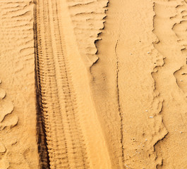 oman desert track of some cars in the sand and direction textu