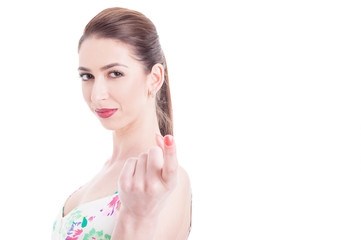 Woman looking at camera making appealing gesture with index fing
