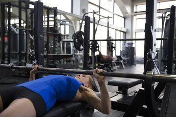 Young Woman Bench Pressing Weights In Gym