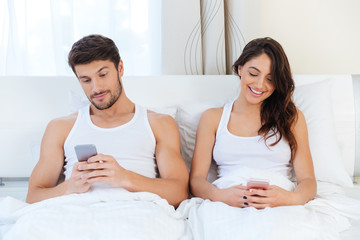 Happy couple in a bed with mobile phones