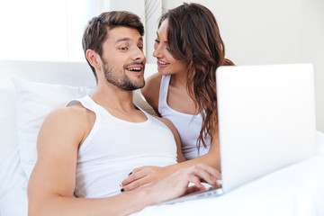 Smiling young couple using laptop in bed