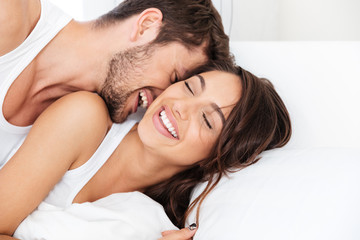 Young happy couple lying in bed